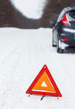 Closeup of red warning triangle with a broken down car Royalty Free Stock Photo