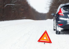 Closeup of red warning triangle with a broken down car Stock Photos