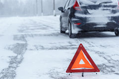 Closeup of red warning triangle with a broken down car in winter Royalty Free Stock Image