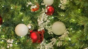 Closeup Red And White Christmas Ornaments On Tree. Closeup of Red and white Christmas Ornaments On Tree with blurred tree branches in right of frame stock images