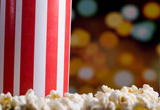 Closeup red white striped container box standing up with popcorn lying around, low angle, flashy vivid lights background Stock Images