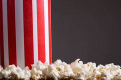 Closeup red white striped container box standing up with popcorn lying around, low angle, grey background Stock Images