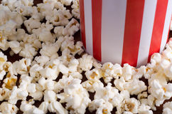 Closeup red white striped container box standing up with popcorn lying around, low angle, grey background.  Royalty Free Stock Photo