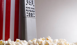 Closeup red white striped container standing up with popcorn lying around, remote control leaning on box, low angle Royalty Free Stock Photos