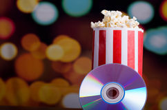 Closeup red white striped container standing up with popcorn reaching over edge, dvd disc leaning on box, low angle Royalty Free Stock Image