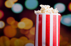 Closeup red white striped container standing up with popcorn reaching over edge, low angle, flashy vivid lights Royalty Free Stock Photography
