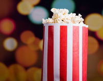 Closeup red white striped container standing up with popcorn reaching over edge, low angle, flashy vivid lights Stock Photos