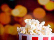 Closeup red white striped container standing up with popcorn reaching over edge, low angle, flashy vivid lights Royalty Free Stock Photo