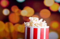 Closeup red white striped container standing up with popcorn reaching over edge, low angle, flashy vivid lights Stock Images