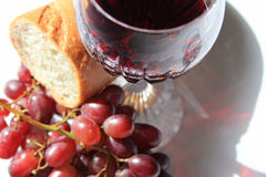 Closeup red wine, bread and grapes Stock Photos