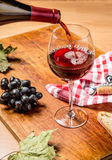 Closeup of red wine pouring in glass Stock Photography