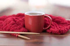 Closeup red yarn ball with knitting needles and scarf in progress lying on desk, coffee mug sitting next to it, blurry. Background Royalty Free Stock Photo