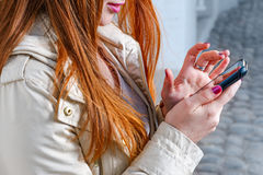 Closeup of redhair girl texting on mobile phone Stock Photos