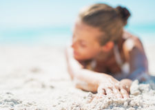 Closeup on relaxed young woman in swimsuit laying on sandy beach Stock Image