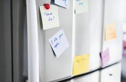 Closeup of reminder paper note on fridge door stock photography