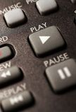 A closeup of a remote control. Focusing on the play button stock image