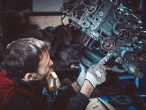 Closeup repair of an opposing engine by an auto mechanic. Diagnosis and disassembly of parts for repair royalty free stock photo