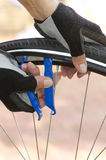 Closeup of repairing bicycle tyre. Detailed image of bicycle repair, with two hands and biker gloves, tools, alloys and blurred background stock photography