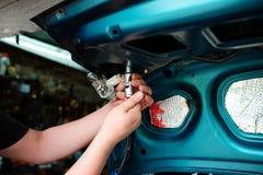 Closeup repairing of an broken blue car in garage by hands of machanic Stock Photo
