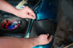 Closeup repairing of an broken blue car in garage by hands of machanic Royalty Free Stock Photography