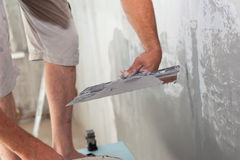 Closeup of repairman hand plastering a wall with putty knife or spatula. stock photography