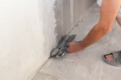 Closeup of repairman hand plastering a wall with putty knife or spatula. royalty free stock photos