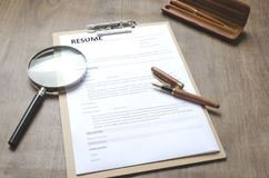 Closeup of a resume application,clipboard,pen, magnifier on wooden table,working process-hiring new people.Concept of hiring new e stock images