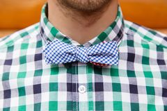 Closeup retro bowtie on a young fashion male. Vintage bowtie on a young fashion male in shirt in front of wooden background Stock Photos