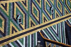 Rhombus and triangle pattern colorful tiles Stephansdom Vienna. Closeup of rhombus and triangle pattern colored glazed tiles and pair of windows on steep sloping royalty free stock photo