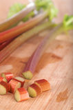Closeup of Rhubarb Stalks and Pieces on Wood Royalty Free Stock Photos