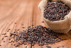 Closeup Rice berry in sack on wood table Royalty Free Stock Photo