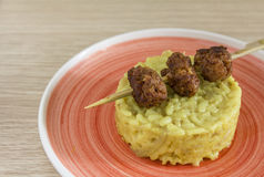 Closeup rice with cabbage and pork meatballs on orange plate wooden background. Rice with cabbage and pork meatballs on orange plate over wooden background stock photos