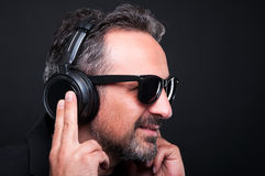 Closeup of rich guy with headphones. Listening music and relaxing isolated on black background Stock Photos