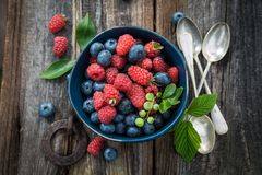 Ripe blueberries and raspberries on old wooden rustic table Stock Image