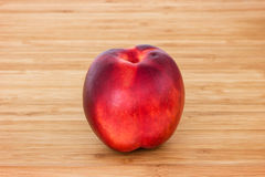 Closeup of a ripe nectarine on a chopping board Royalty Free Stock Image
