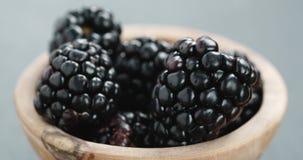 Closeup of ripe organic blackberries in wood bowl on slate background royalty free stock photo