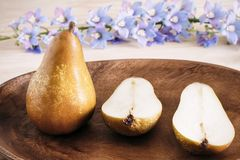 Closeup ripe pears on a wooden vintage plate on the table, sweet fruit dessert, autumn harvest, diet products, place for text stock images