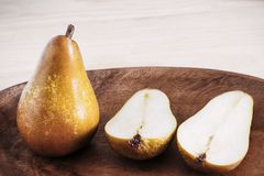 Closeup ripe pears on a wooden vintage plate on the table, sweet fruit dessert, autumn harvest, diet products, place for text stock photos