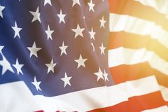 Sunny USA flag. Closeup of rippled American flag. Sunlight shining from end of Stock Photo