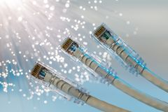 Closeup of RJ45 UTP LAN on the background of optical fibers with blurred lights.  stock photography