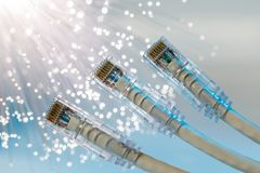 Closeup of RJ45 UTP LAN on the background of optical fibers with blurred lights.  royalty free stock photo