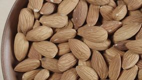 Closeup roasted almonds in wooden bowl. 4K stock video