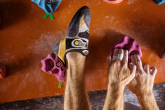 Closeup of rock climber`s hands and foot on holds in indoor clim. Cropped view of rock climber`s hands and foot on holds in indoor climbing gym Royalty Free Stock Images