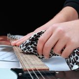 Closeup.rock guitarist,wiping the neck of the guitar. Photo with copy space stock image