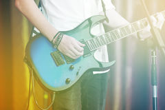 Closeup rockstar on stage playing on electro guitar. Male guitarist in a white shirt.  Royalty Free Stock Images
