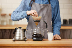 Closeup of rofessional bartender preparing pourover coffee in chemex. Stock Photo