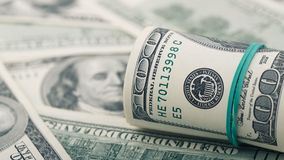 Closeup rolled dollar hundred on background American money dollar bill. Many US 100 banknote royalty free stock photos