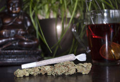 Closeup of rolled marijuana weed joint and buds on wooden background, with Buddha statuette. And cup of rooibos tea Stock Photography