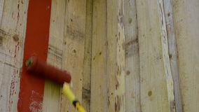 Closeup of roller brush paint wooden plank house wall stock video