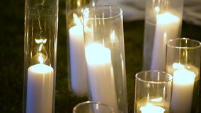 Closeup Romantic burning white candles in glass vases standing on a grass for an evening wedding ceremony. stock footage